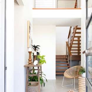 Inspiration for a tropical entry hall in Sunshine Coast with white walls, a single front door, a glass front door and beige floor.