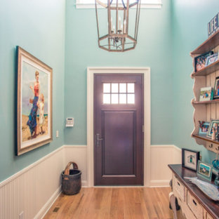 Example of a mid-sized beach style light wood floor entryway design in Orange County with blue walls and a dark wood front door
