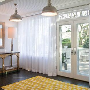 ニューヨークの巨大な両開きドアビーチスタイルのおしゃれなマッドルーム (白い壁、濃色無垢フローリング、白いドア) の写真