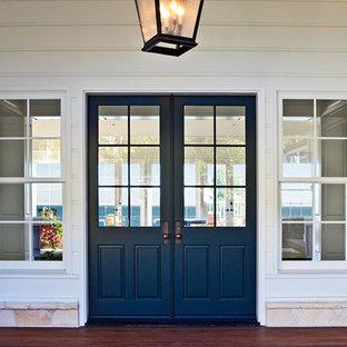 На фото: входная дверь среднего размера в классическом стиле с белыми стенами, темным паркетным полом, двустворчатой входной дверью и синей входной дверью с
