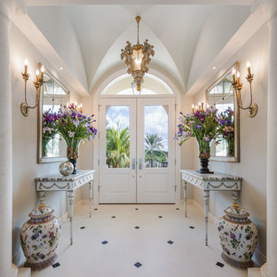 Entryway - traditional limestone floor entryway idea in Tampa with gray walls and a white front door
