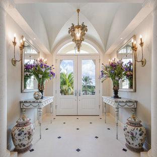 Пример оригинального дизайна: фойе в классическом стиле с серыми стенами, полом из известняка, двустворчатой входной дверью и белой входной дверью