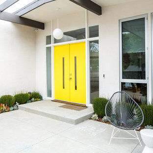 Idéer för 60 tals ingångspartier, med vita väggar, betonggolv, en dubbeldörr, en gul dörr och grått golv