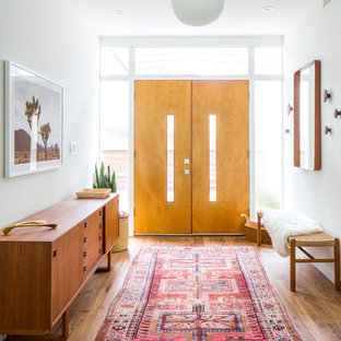Mid-century modern medium tone wood floor and brown floor entryway photo in Los Angeles with white walls and a light wood front door