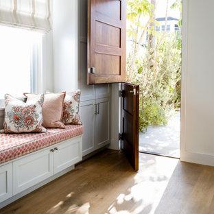 Ejemplo de vestíbulo posterior marinero, de tamaño medio, con paredes blancas, suelo de madera clara, puerta tipo holandesa, puerta de madera en tonos medios y suelo beige