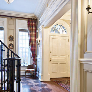 Example of a classic brown floor and medium tone wood floor entryway design in New York with beige walls and a white front door