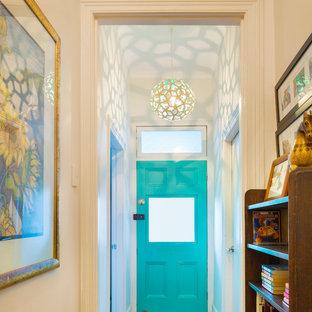 Immagine di un piccolo corridoio stile marinaro con pareti bianche, pavimento in legno massello medio, una porta singola e una porta blu