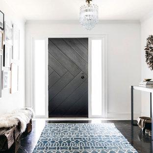 Inspiration för klassiska foajéer, med vita väggar, mörkt trägolv, en enkeldörr, en svart dörr och brunt golv