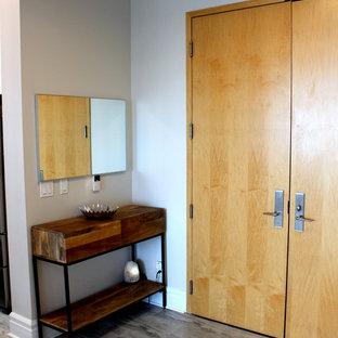Exemple d'un hall d'entrée tendance de taille moyenne avec un mur gris, un sol en carrelage de porcelaine, une porte double, une porte en bois clair et un sol gris.