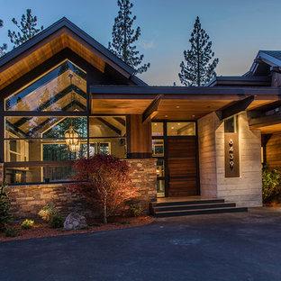 На фото: большое фойе в современном стиле с бетонным полом, поворотной входной дверью и входной дверью из дерева среднего тона с