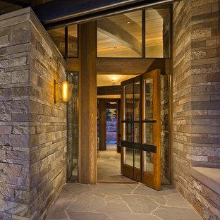 Стильный дизайн: большая входная дверь в стиле рустика с серыми стенами, поворотной входной дверью, стеклянной входной дверью и гранитным полом - последний тренд