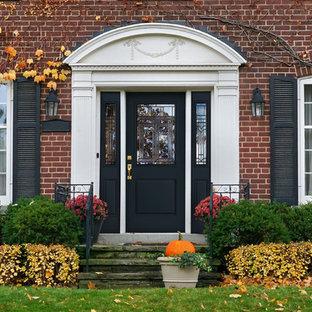 Modelo de puerta principal tradicional, extra grande, con paredes rojas, suelo de cemento, puerta simple, puerta azul y suelo gris
