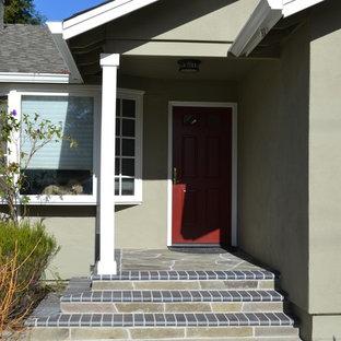 Modelo de puerta principal tradicional renovada, de tamaño medio, con paredes verdes, suelo de pizarra, puerta simple y puerta roja