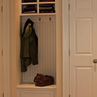 Idéer för ett litet klassiskt kapprum, med gula väggar, mörkt trägolv, en enkeldörr, en vit dörr och brunt golv