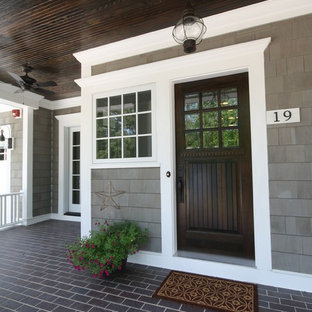 This is an example of a beach style front door in Chicago with a single front door and a dark wood front door.