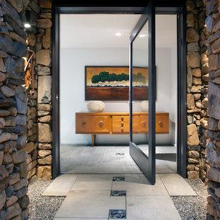 Idee per una porta d'ingresso minimal di medie dimensioni con una porta a pivot, una porta in vetro, pareti beige, pavimento in ardesia e pavimento beige