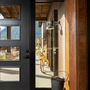 Foto på en mellanstor industriell foajé, med orange väggar, betonggolv, en enkeldörr, en svart dörr och grått golv