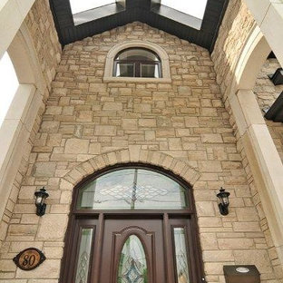 Example of a classic entryway design in Toronto with beige walls and a dark wood front door