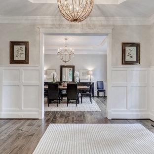 Exempel på en mellanstor klassisk entré, med vita väggar, plywoodgolv, en enkeldörr och mörk trädörr