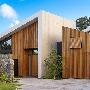 Inspiration för en stor funkis ingång och ytterdörr, med en enkeldörr, mellanmörk trädörr, bruna väggar och grått golv