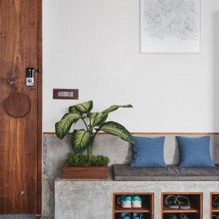 アフマダーバードのコンテンポラリースタイルのおしゃれな玄関 (白い壁、コンクリートの床、木目調のドア、グレーの床) の写真