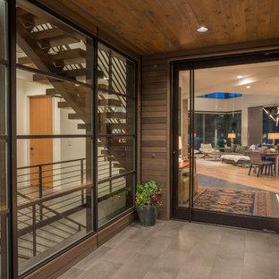 Idéer för att renovera en stor funkis ingång och ytterdörr, med beige väggar, klinkergolv i porslin, en pivotdörr, glasdörr och beiget golv