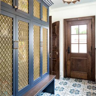 Bild på ett medelhavsstil kapprum, med vita väggar, klinkergolv i keramik, en brun dörr och blått golv