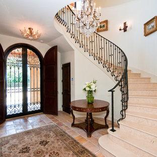 Пример оригинального дизайна: большое фойе в средиземноморском стиле с двустворчатой входной дверью, входной дверью из темного дерева, белыми стенами и полом из керамической плитки