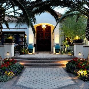 Inspiration for a mediterranean double front door remodel in Phoenix with a dark wood front door