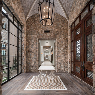Example of a tuscan medium tone wood floor and brown floor entryway design in Phoenix with gray walls and a medium wood front door