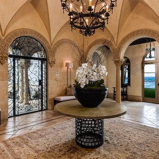 Idée de décoration pour un hall d'entrée méditerranéen avec un mur beige et une porte métallisée.