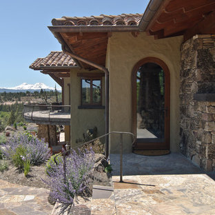 Example of a tuscan single front door design in Other with a glass front door