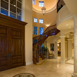 Tuscan entryway photo in Tampa with beige walls and a dark wood front door