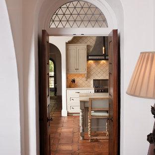 На фото: прихожая в средиземноморском стиле с двустворчатой входной дверью, входной дверью из темного дерева и полом из терракотовой плитки