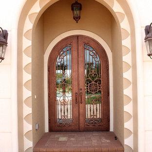 Источник вдохновения для домашнего уюта: большая входная дверь в средиземноморском стиле с двустворчатой входной дверью и металлической входной дверью
