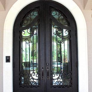 Idée de décoration pour une grand porte d'entrée méditerranéenne avec une porte double et une porte métallisée.