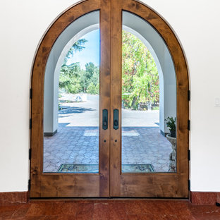 Immagine di una grande porta d'ingresso mediterranea con pareti beige, pavimento in terracotta, una porta a due ante e una porta in legno bruno