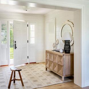 Inspiration för en maritim entré, med vita väggar, mellanmörkt trägolv, en enkeldörr, en vit dörr och brunt golv