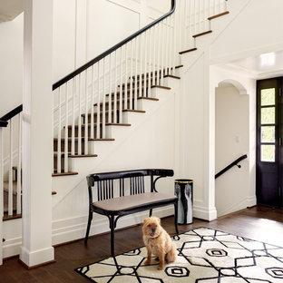 Пример оригинального дизайна: фойе в стиле неоклассика (современная классика) с белыми стенами, темным паркетным полом, черной входной дверью и коричневым полом