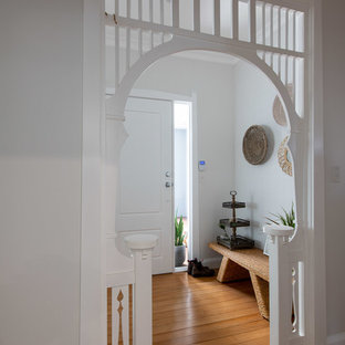This is an example of a transitional foyer in Newcastle - Maitland with white walls, medium hardwood floors, a single front door, a white front door and brown floor.