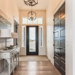 Идея дизайна: фойе в стиле кантри с белыми стенами, светлым паркетным полом, одностворчатой входной дверью, черной входной дверью и правильным освещением