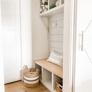 Inredning av ett klassiskt litet kapprum, med vita väggar, ljust trägolv, en enkeldörr, en vit dörr och beiget golv