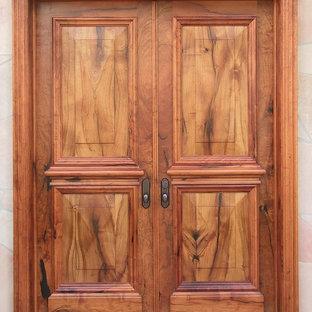 フェニックスの広い両開きドアトラディショナルスタイルのおしゃれな玄関ドア (ベージュの壁、テラゾーの床、木目調のドア) の写真