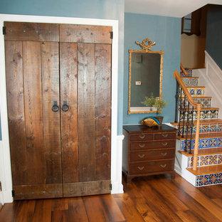 Exemple d'un petit hall d'entrée sud-ouest américain avec un sol en bois brun, un mur bleu, une porte simple et une porte blanche.