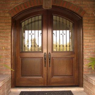 Пример оригинального дизайна: большая входная дверь в классическом стиле с оранжевыми стенами, полом из терракотовой плитки, двустворчатой входной дверью и входной дверью из дерева среднего тона