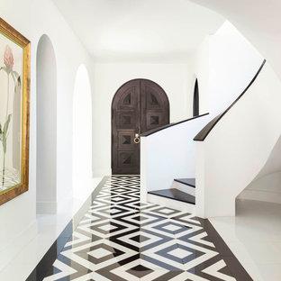 Medelhavsstil inredning av en hall, med vita väggar, marmorgolv, en dubbeldörr, mörk trädörr och flerfärgat golv