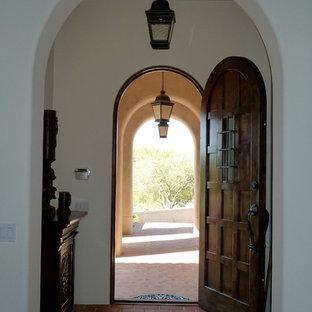 Foto de puerta principal mediterránea, de tamaño medio, con paredes blancas, suelo de baldosas de terracota, puerta simple y puerta de madera oscura