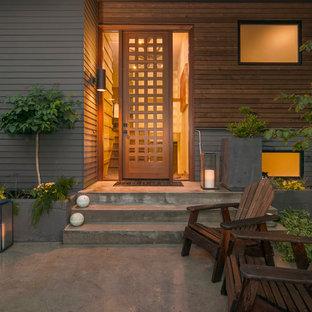 Foto på en mellanstor 60 tals ingång och ytterdörr, med grå väggar, betonggolv, en enkeldörr och mellanmörk trädörr