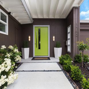 Idée de décoration pour une porte d'entrée vintage avec un mur marron, une porte simple, une porte verte et un sol jaune.