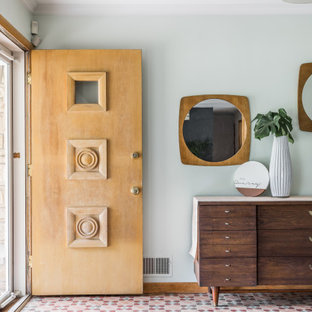 Design ideas for a midcentury entryway in Indianapolis with blue walls, a single front door and multi-coloured floor.